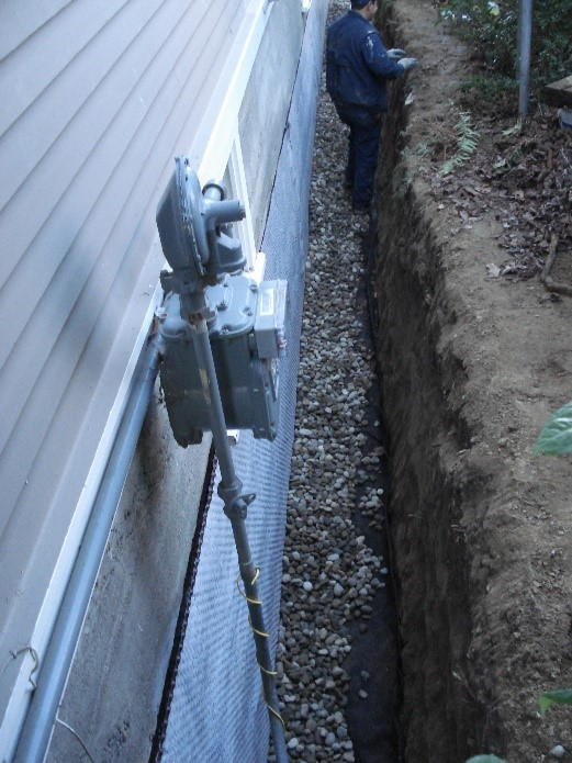 New footing drain with coating, drain mat and rock.